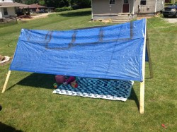 Make your own tent with a tarp and scrap wood.